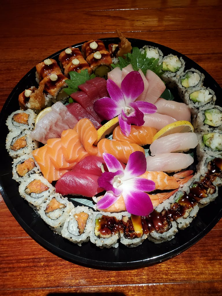 sushi on a wooden table topped with plates of food on a plate