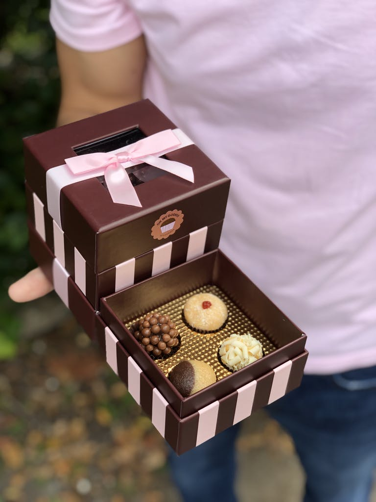 a person holding a box of sweets