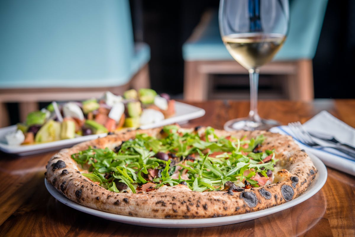 a pizza with a wine glass on a table