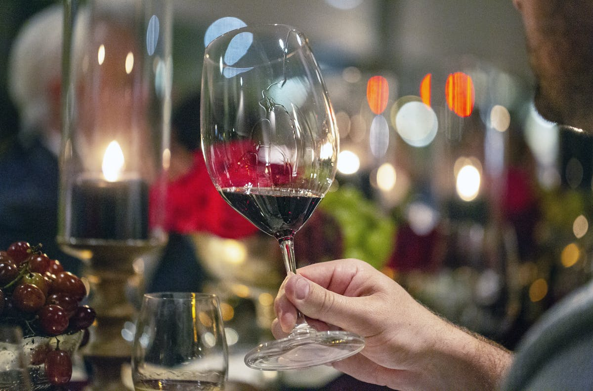 a close up of a person holding a wine glass