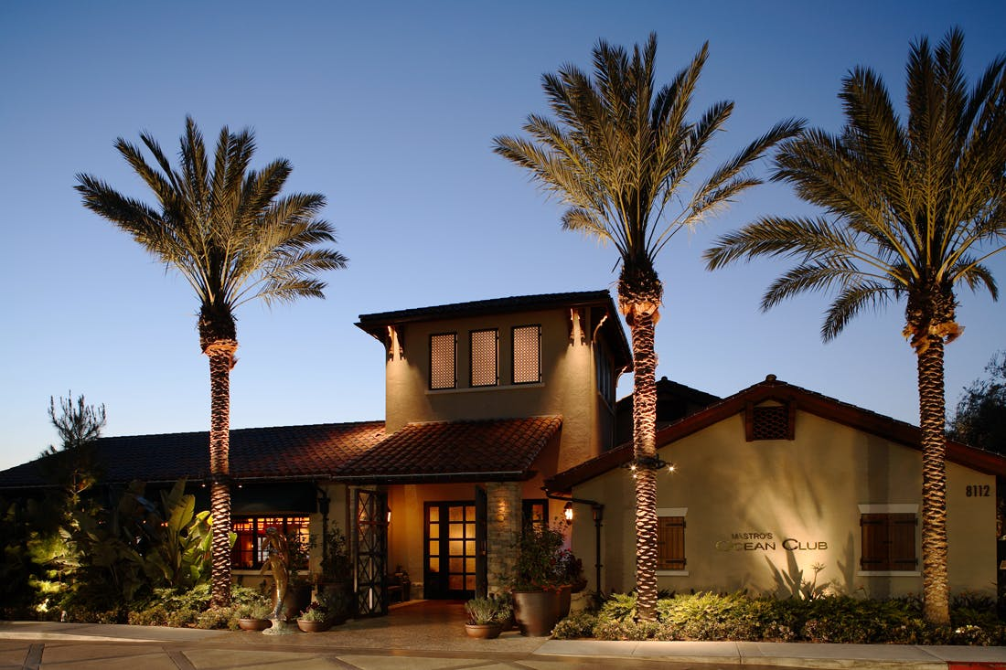 a restaurant building with palm trees