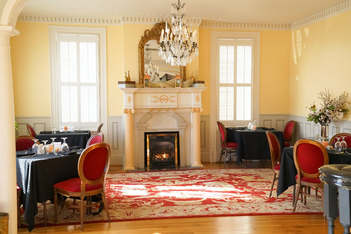 a fancy looking dining room filled with tables and a chimney