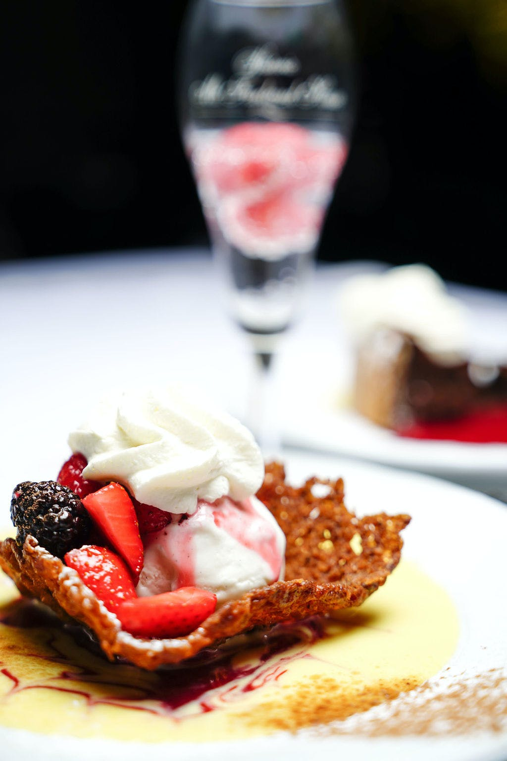a close up of a chocolate dessert topped with whipped cream and strawberries and blueberries