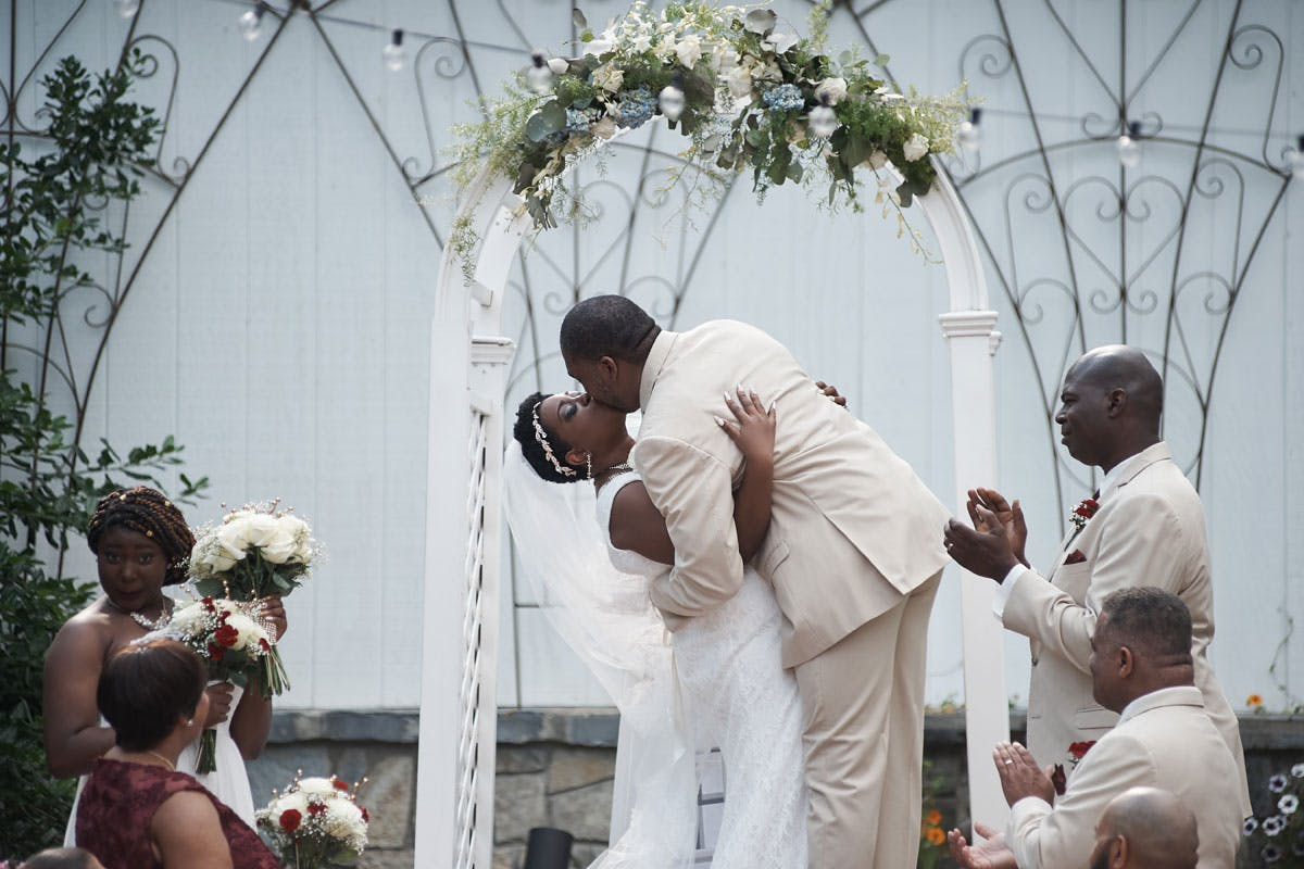 a close up of Halima & Kenneth kissing at the altar