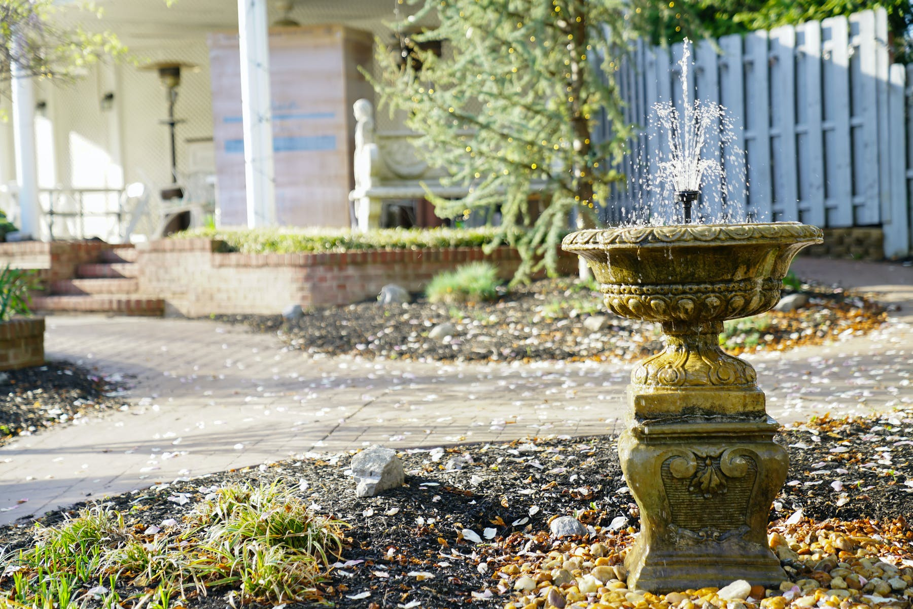a fountain in front of a house garden