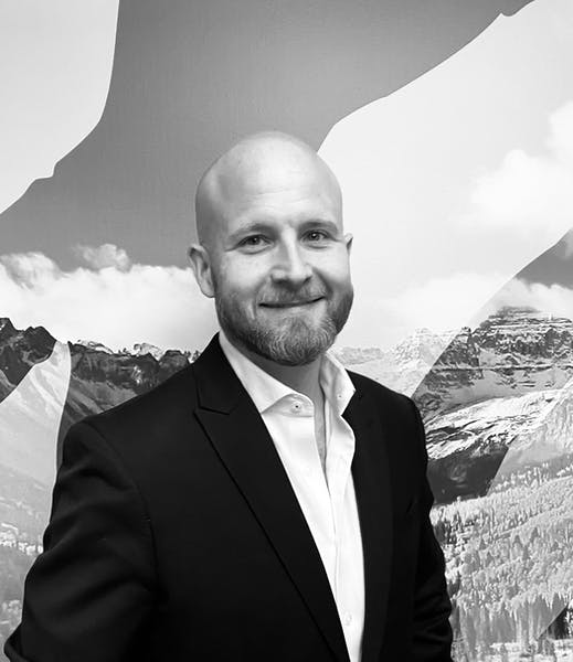 a man wearing a suit and tie standing in front of a mountain