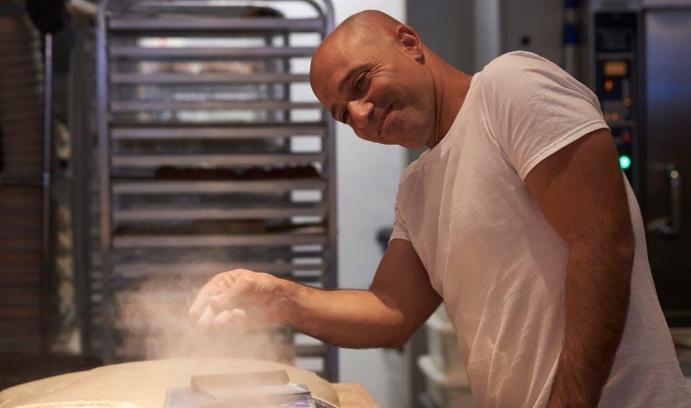 A baker throwing flour on a counter top while mixing dough.