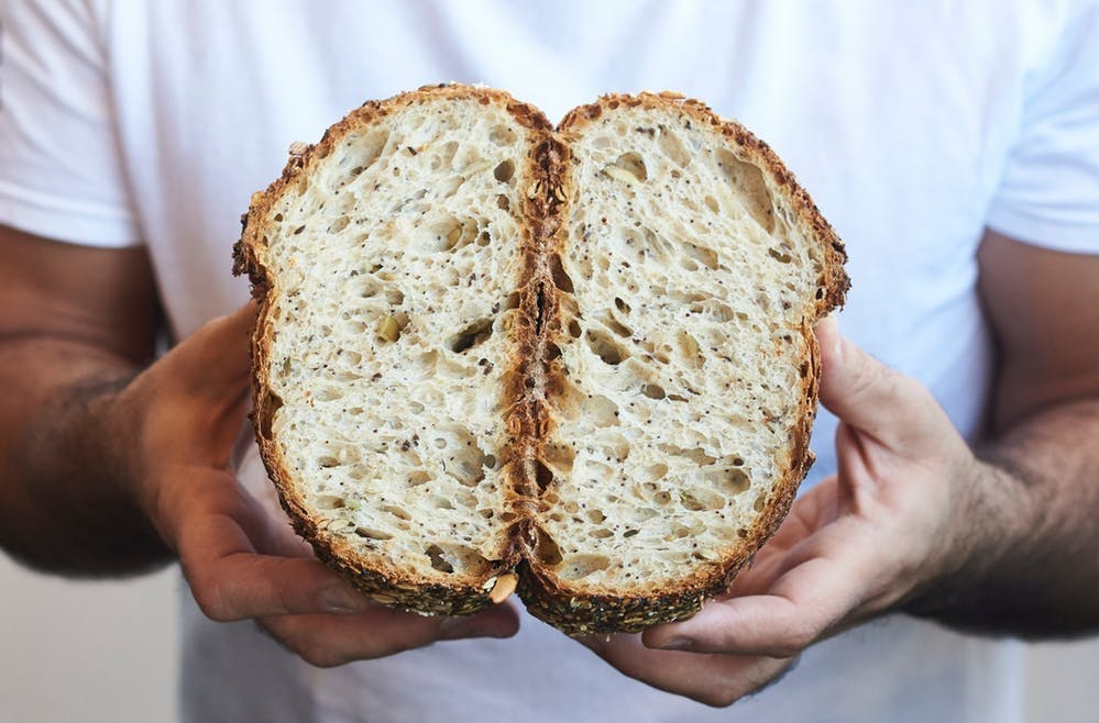 A man holding a loaf of bread that has been cut in half.
