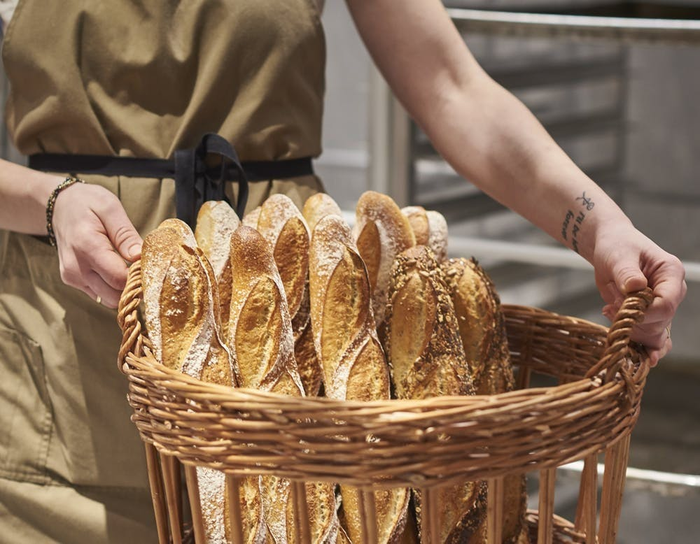 A woman holding a basket of freshly baked bread loaves.