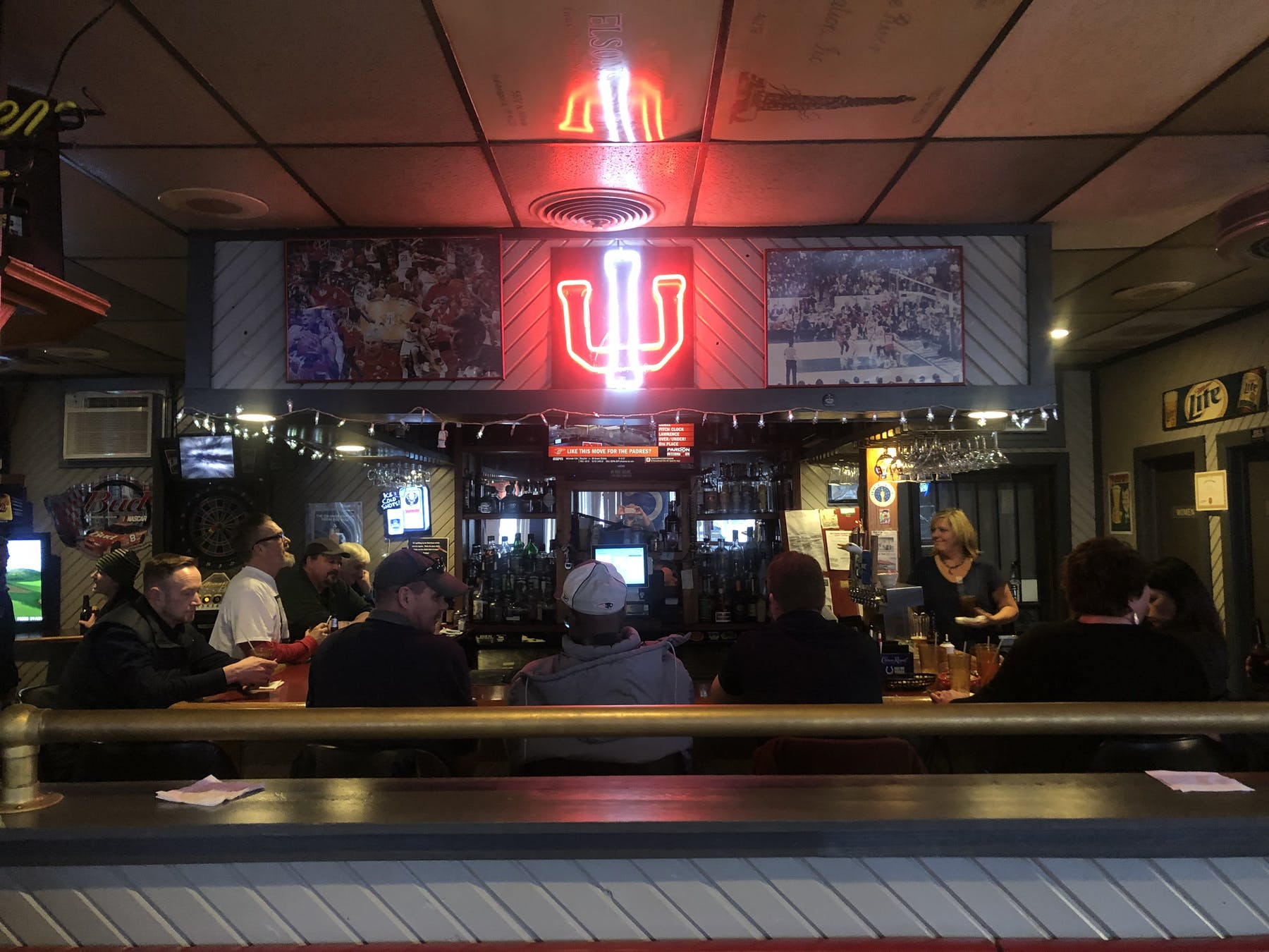 Darkly lit bar with light up IU sign on wall.